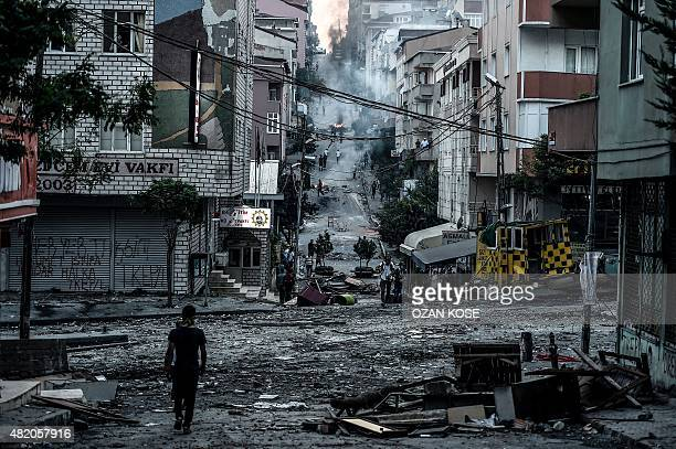 A protester walks by the Cemevi square during clashes with Turkish riot police in Istanbul's Gazi district on July 26 2015 A Turkish policeman was...