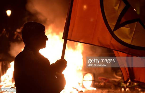 A protester walks in front of a fire after the 'Welcome to Hell' rally against the G20 summit in Hamburg northern Germany on July 6 2017 Leaders of...
