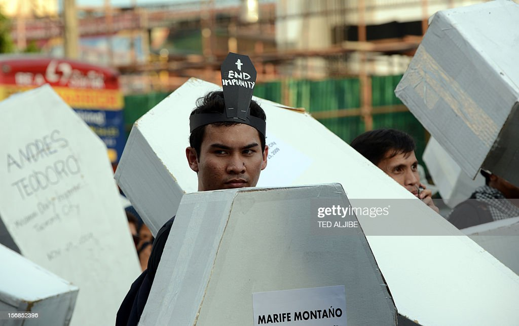 A protester walks next to mock coffins during a march protest to Malacanang Palace in Manila on November 23, 2012, to commemorate the third anniversary of the November 23 Maguindanao massacre. Dozens of members of a clan whose leaders are on trial for the Philippines' worst political massacre are candidates in 2013 elections, some for the president's party, media and rights groups said November 23. The revelations sparked outrage on the three-year anniversary of the massacre, in which 58 people died, with critics saying the Ampatuan family's enduring political influence underlined the country's 'culture of impunity'.