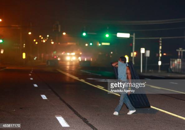 A protester walks on the road with his belonging during a demonstration on August 18 2014 for Michael Brown who was killed by a police officer on...