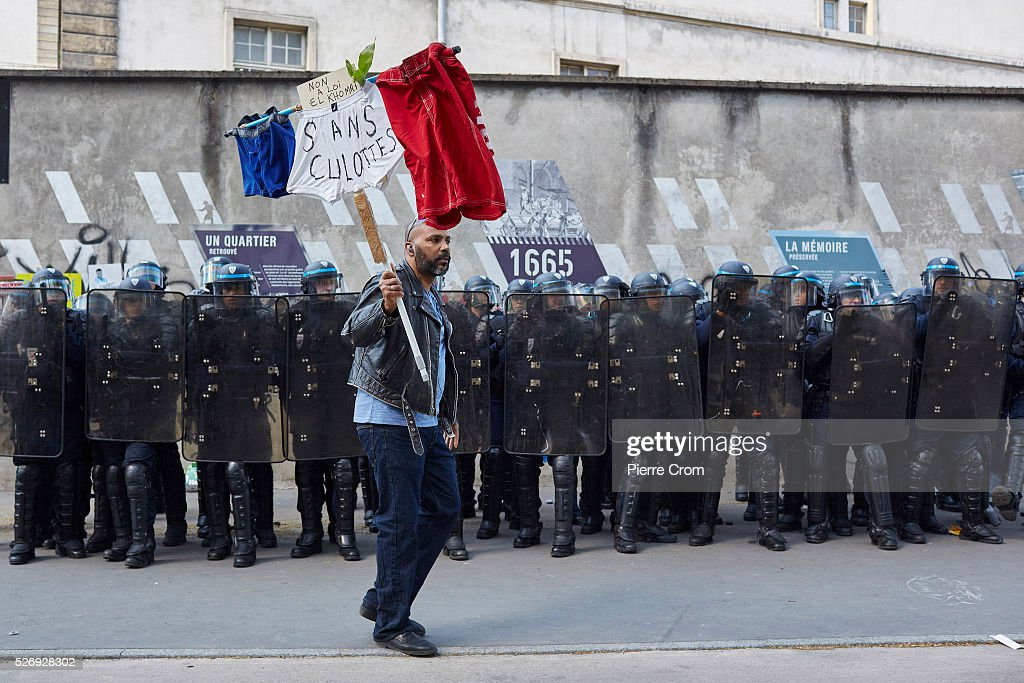 A protester walks past a line of riot police during a May Day rally on May 01, 2016 in Paris, France. Violence broke out as people took to the streets to demonstrate against proposed labour law reforms.