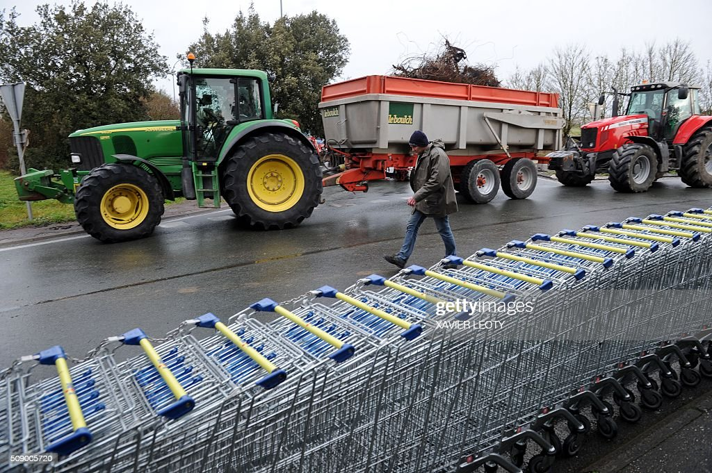 A protester walks past shopping trolleys and tractors as he and others block a road near Saintes, western France, on February 8, 2016, during a demonstration by farmers against the purchase price of their products by supermarkets. Over 100 tractors were used by mostly pig and dairy farmers to block strategic points giving access to the city, disrupting traffic and closing an interchange of the A10 motorway. / AFP / XAVIER LEOTY