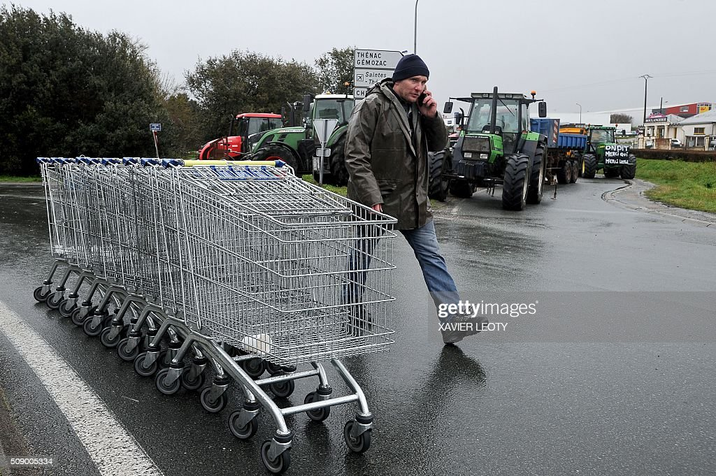 A protester walks past tractors and shopping trolleys as he and others block a road near Saintes, western France, on February 8, 2016, during a demonstration against the purchase price of their products by supermarkets. Over 100 tractors were used by mostly pig and dairy farmers to block strategic points giving access to the city, disrupting traffic and closing an interchange of the A10 motorway. / AFP / XAVIER LEOTY