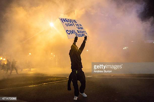 A protester walks through tear gas as police enforce a mandatory citywide curfew of 10PM near the CVS pharmacy that was set on fire yesterday during...