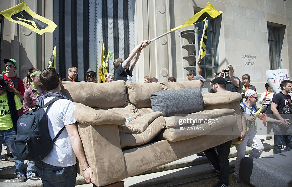 Protester wave flags as other carry a couch in front of the US Department of Justice after the demonstrators forced security inside during a rally against big banks and home foreclosures in Washington, DC, May 20, 2013.