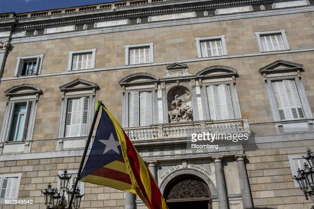 A protester waves a Catalan independence flag also known as the Estelada outside the Generalitat during a silent demonstration in support of arrested...