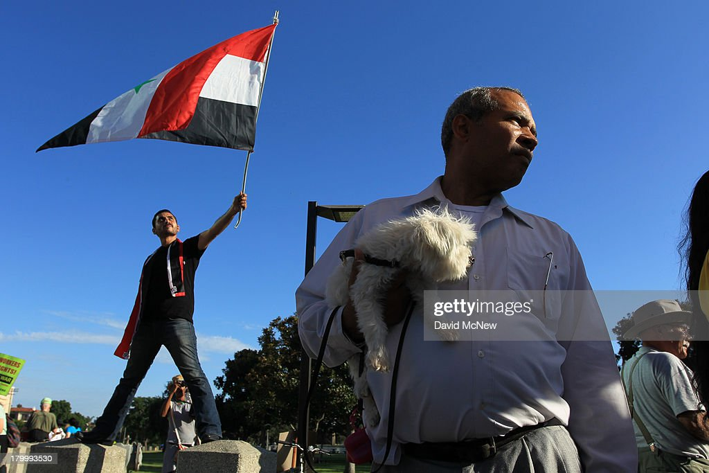 A protester waves a flag at a rally to urge Congress to vote against a limited military strike against the Syrian military in response to allegations that President Bashar Hafez al-Assad has used sarin gas to kill civilians on September 7, 2013 in Los Angeles, California. The Obama administration claims to have clear evidence that the Syrian military broke international law by killing nearly 1,500 Syrian civilians, including at least 426 children, in a chemical weapons attack on August 21, and is seeking the support of Congress for a missile strikes to prevent future chemical weapons attacks by the regime and other nations.