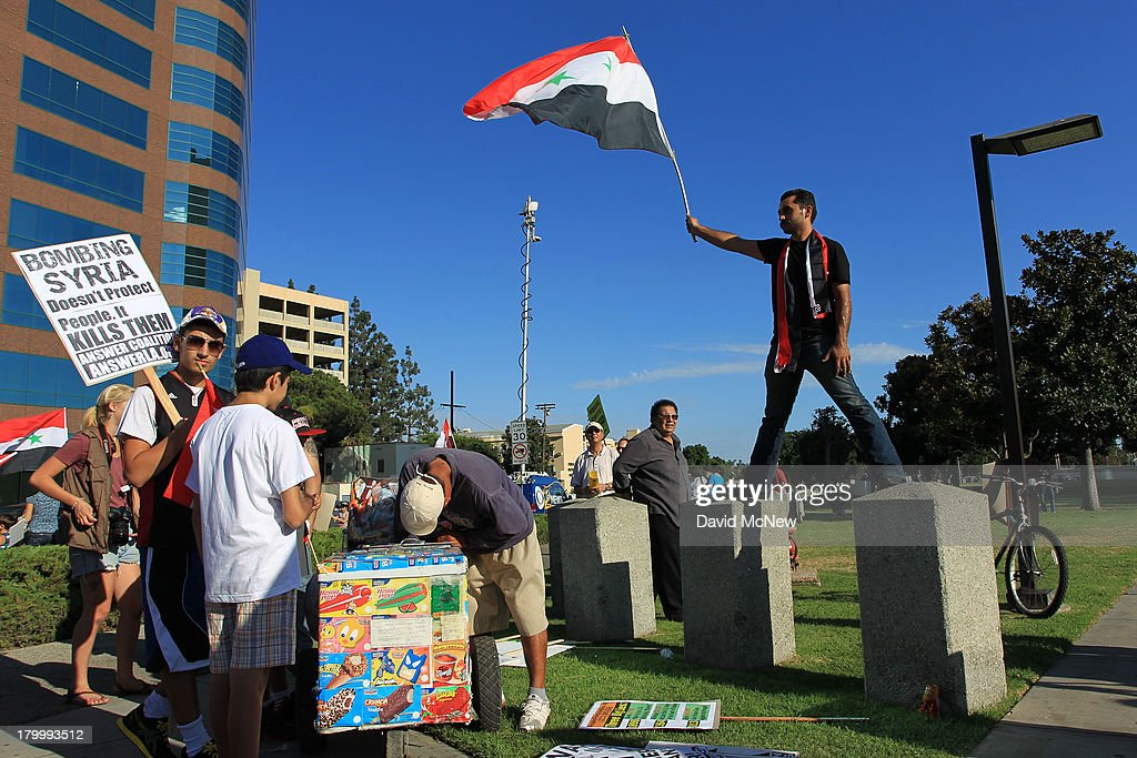 A protester waves a flag near an ice cream vendor at a rally to urge Congress to vote against a limited military strike against the Syrian military in response to allegations that President Bashar Hafez al-Assad has used sarin gas to kill civilians on September 7, 2013 in Los Angeles, California. The Obama administration claims to have clear evidence that the Syrian military broke international law by killing nearly 1,500 Syrian civilians, including at least 426 children, in a chemical weapons attack on August 21, and is seeking the support of Congress for a missile strikes to prevent future chemical weapons attacks by the regime and other nations.