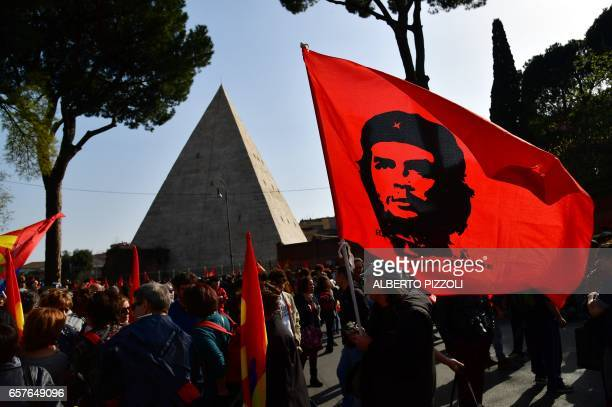 A protester waves a flag showing a portrait of Ernesto Che Guevara during a demonstration against Europe near the Pyramid of Cestius on March 25 2017...