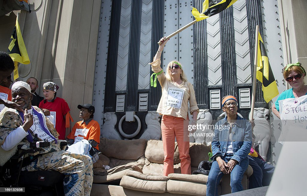 A protester waves a flag while standing on a couch in front of the US Department of Justice after the demonstrators forced security inside during a rally against big banks and home foreclosures in Washington, DC, May 20, 2013.