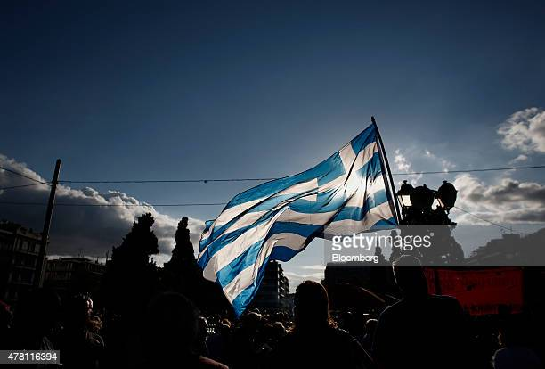 A protester waves a Greek national flag during a pro European Union demonstration in Athens Greece on Monday June 22 2015 European policy makers...
