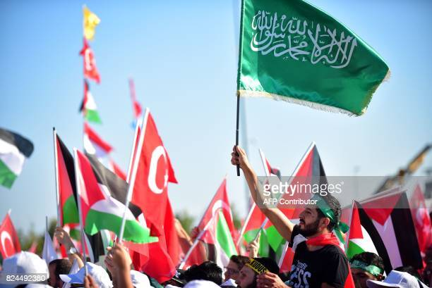A protester waves a green Islamic flag with the Muslim profession of belief 'There is no God but God and Mohammed is the prophet of God' during a...