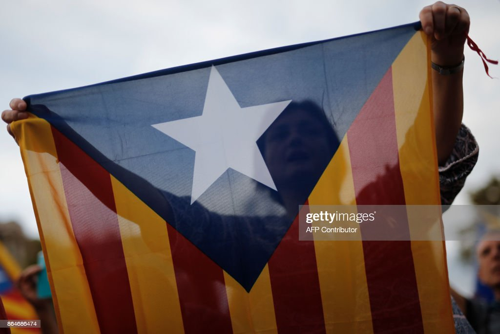 A protester waves a pro-independence Catalan Estelada flag during a demonstration in Barcelona on October 21, 2017 in support of two separatist leaders Jordi Sanchez and Jordi Cuixart, who have been detained pending an investigation into sedition charges. Spain announced that it will move to dismiss Catalonia's separatist government and call fresh elections in the semi-autonomous region in a bid to stop its leaders from declaring independence. /