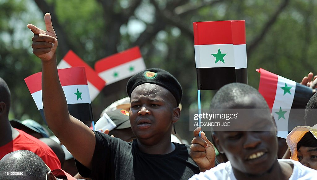 A protester waves a Syrian flag as Syrians and members of the Congress of South African Trade Unions (COSATU) gather outside the US embassy in Pretoria on October 11, 2013 during a protest against US intervention in Syria and the conflict in the war-torn country which they consider to be 'in the interest of imperialism'. AFP PHOTO / ALEXANDER JOE