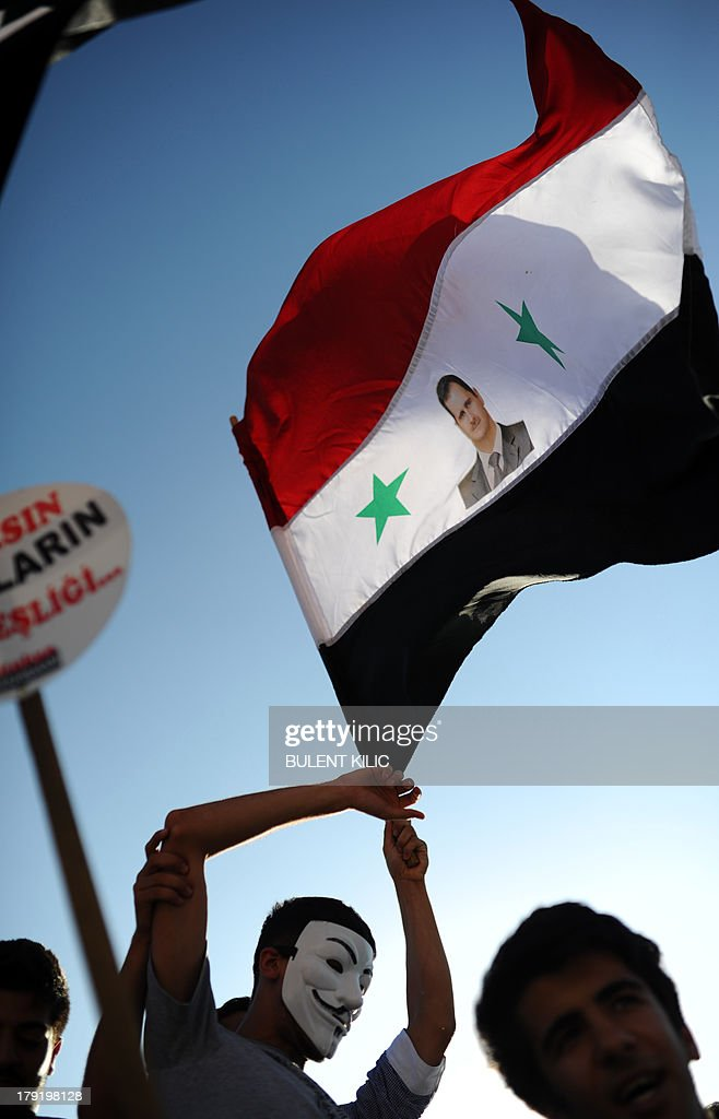 A protester waves a Syrian flag with the photograph of Syrian President Bashar al-Assad during a rally against a possible attack on Syria in response to alleged use of chemical weapons by the Assad government on September 1, 2013, in Hatay. US President Barack Obama said on September 1 he will ask the US Congress to authorize military action against Syria, lifting the threat of immediate strikes on President Bashar al-Assad's regime. Obama said he had decided he would go ahead and launch military action on Syria, but he believed it was important for American democracy to win the support of lawmakers.