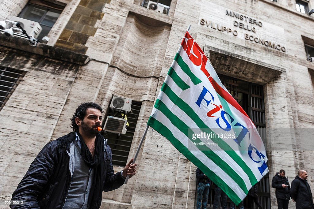 A protester waves a trade union flag as he takes a rally to protest against dismissal of 450 workers. A group of call center employees of Gepin (former Poste Italiane) hold a rally in Rome, in front of the Ministry of Economic Development, to protest against layoffs.