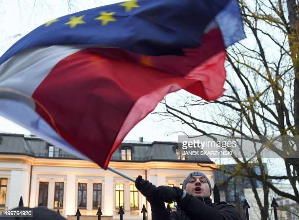Protester waves flags of Poland and the European Union in front of the Polish Constitutional Court following a sentence regarding the appointment of...