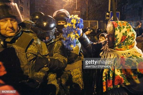 A protester waves flowers to a policeman during a rally against trade with the occupied territories in Kiev on February 19 2017 More than a thousand...