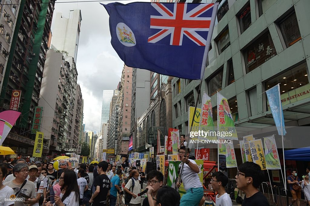 A protester waves Hong Kong's former colonial flag during a pro-democracy rally in Hong Kong on July 1, 2016, traditionally a day of protest which also marks the anniversary of the handover from Britain to China in 1997. Protesters took to the streets of Hong Kong on July 1 to mark the anniversary of the city's handover from Britain to China, with pro-independence groups rallying for the first time amid fears Beijing is tightening its grip. / AFP / ANTHONY