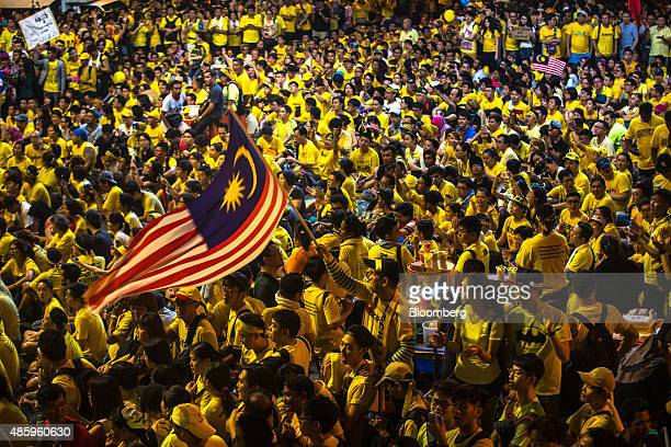 A protester waves the Malaysian Flag around a large crowd gathered around the Dataran Merdeka during the Coalition for Clean and Fair Elections rally...