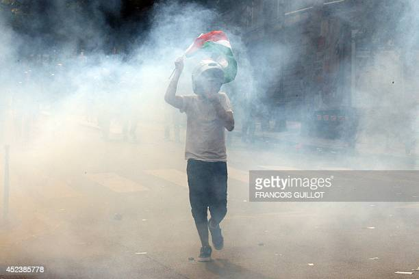 A protester waving a Palestinian flag is seen through tear gars near the aerial metro station of BarbesRochechouart in Paris on July 19 during...