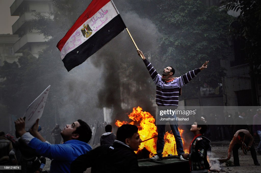 A protester waving the Egyptian flag as the army soldiers throw rocks at protesters from a rooftop that overlooks the Qasr Ainy street, off Tahrir Square. On December 16, 2011 military police abducted a protester 'Abboudy' from the cabinet sit-in in Qasr Ainy street near Tahrir square. Abboudy was badly beaten and tortured by military forces. Hours later clashes erupted between protesters and military forces leading to a non-stop battle that lasted for more than 48 hours.More than ten were killed in the clashes.