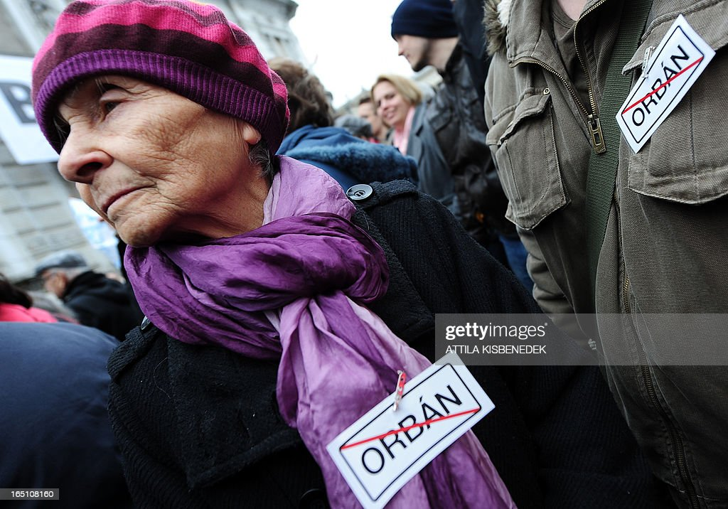 Protester wear anti Hungarian Prime Minister Viktor Orban stickers during an anti-government demonstration in front of the headquarters of the FIDESZ paty in Budapest on March 30, 2013. The fourth constitutional modification of the basic law will be come into force on April 1. AFP PHOTO / ATTILA KISBENEDEK