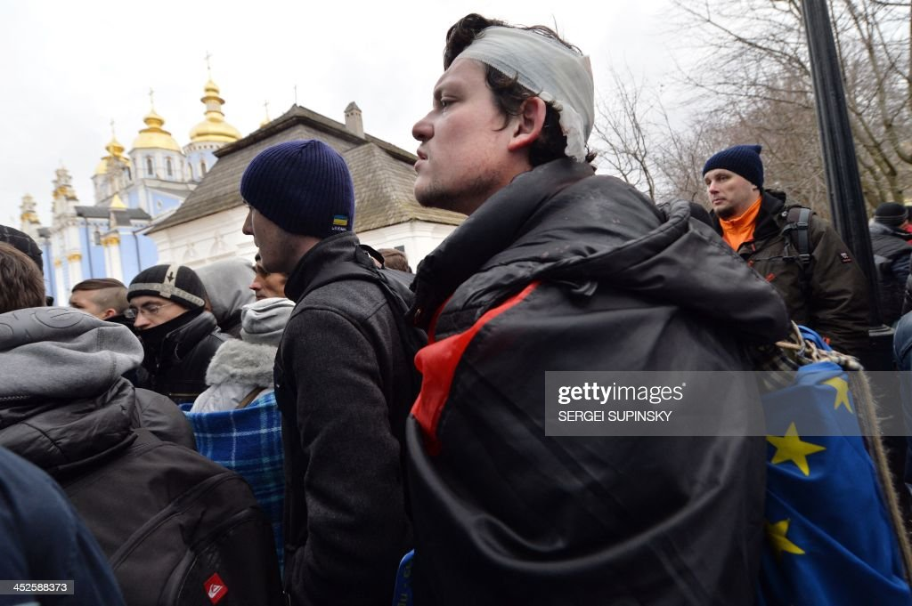 A protester, wearing a bandage around his head after he was injured in clashes with police, holds a flag of the European Union aas he and others take shelter in Mykhaylo Gold Dome cathedral on November 30, 2013. Dozens of protesters were wounded in Ukraine's capital early Saturday when police brutally dispersed demonstrators calling for President Viktor Yanukovych's ouster after he failed to salvage an EU deal, a lawmaker and a witness said. 'The Maidan has been brutally mopped up,' opposition lawmaker Andriy Shevchenko said on Twitter, referring to Kiev's central Independence Square, the site of the rally and epicentre of the country's 2004 Orange Revolution. SUPINSKY