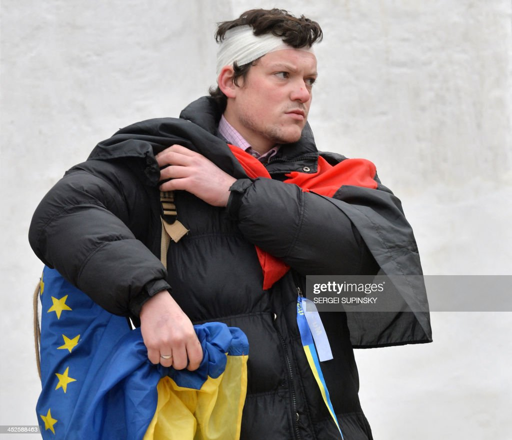 A protester, wearing a bandage around his head, holds a Ukrainian and an European Union flags as he and others take shelter in the Mykhaylo Gold Dome cathedral after clashing with police on Independence Square in Kiev early morning on November 30, 2013. Dozens of protesters were wounded in Ukraine's capital early Saturday when police brutally dispersed demonstrators calling for President Viktor Yanukovych's ouster after he failed to salvage an EU deal, a lawmaker and a witness said. 'The Maidan has been brutally mopped up,' opposition lawmaker Andriy Shevchenko said on Twitter, referring to Kiev's central Independence Square, the site of the rally and epicentre of the country's 2004 Orange Revolution. SUPINSKY