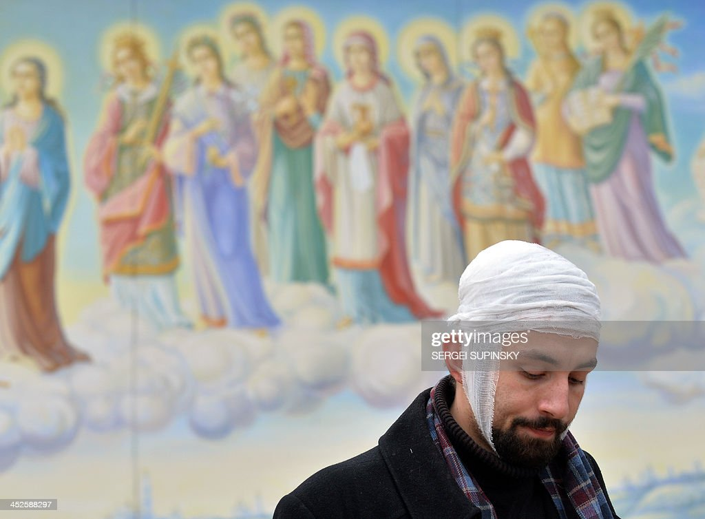 A protester, wearing a bandage around his head, stands in front of a fresco as he and others take shelter in the Mykhaylo Gold Dome cathedral, after he was injured in clashes with police on Independence Square in Kiev early morning on November 30, 2013. Dozens of protesters were wounded in Ukraine's capital early Saturday when police brutally dispersed demonstrators calling for President Viktor Yanukovych's ouster after he failed to salvage an EU deal, a lawmaker and a witness said. 'The Maidan has been brutally mopped up,' opposition lawmaker Andriy Shevchenko said on Twitter, referring to Kiev's central Independence Square, the site of the rally and epicentre of the country's 2004 Orange Revolution. SUPINSKY