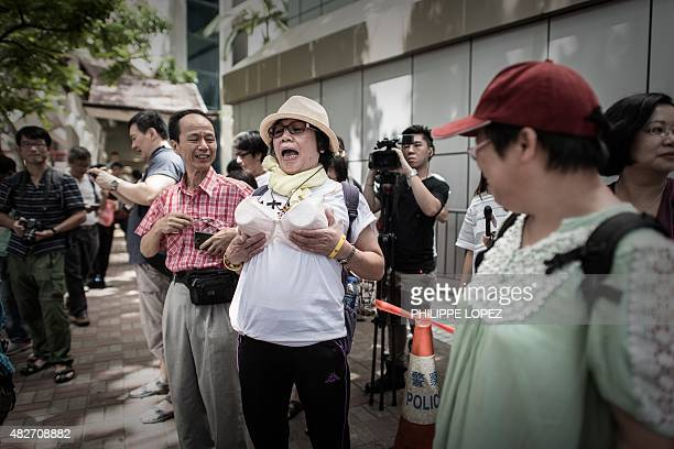 A protester wearing a bra reacts during a demonstration outside the police headquarters in Hong Kong on August 2 2015 The demonstrators gathered in...