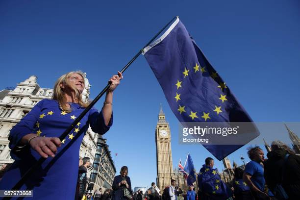 A protester wearing a dress in the style of a European Union flag holds an EU flag in front of Elizabeth Tower commonly referred to as Big Ben during...