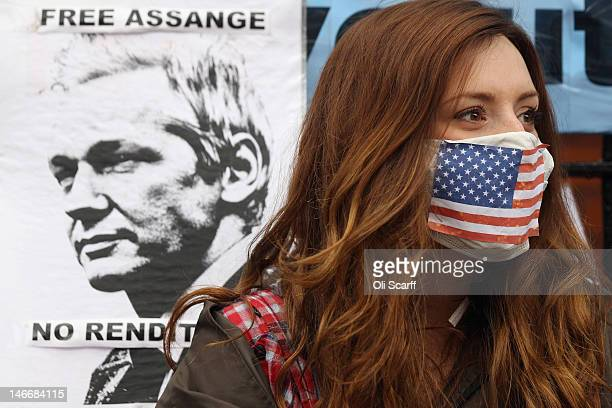 A protester wearing a face mask displaying the American national flag next to a placard displaying an image of Julian Assange shows her support for...