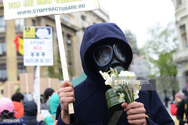 A protester wearing a gas mask holds a placard during a protest against shale gas exploiting in Bucharest on April 6 2014 Hundreds of people gathered...