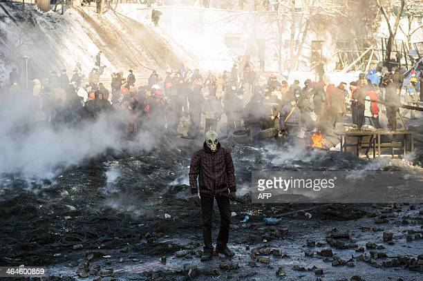 A protester wearing a gas mask stands amid burnt tyres and garbage following clashes between proEU demonstrators and riot police in Kiev on January...