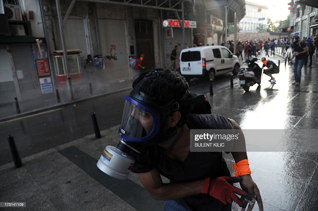A protester, wearing a gas mask, stands in a street during clashes with Turkish riot policemen on Istiklal avenue, in Istanbul on July 8, 2013. Turkish riot police fired rubber bullets, tear gas and water cannon to block demonstrators from entering a small Istanbul park, the birthplace of deadly unrest that engulfed the country last month.