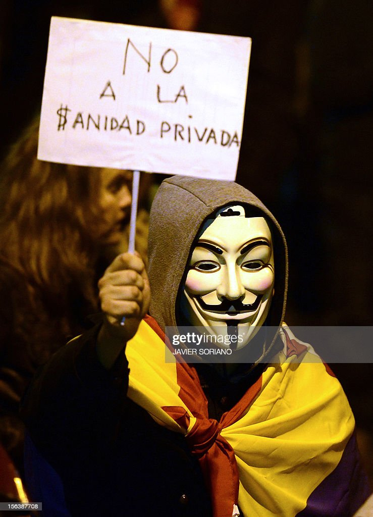 A protester wearing a Guy Fawkes mask holds a placard reading 'No to the healthcare privatization' as protesters attend a demonstration during a general strike on November 14, 2012 in Madrid. The second general strike this year hit Spain with protesters marching in several cities against sweeping austerity measures and high unemployment, scenes echoed elsewhere in Europe. Spain, the eurozone's fourth-biggest economy, is suffering 25 percent unemployment, with the rate even higher amongst young people.