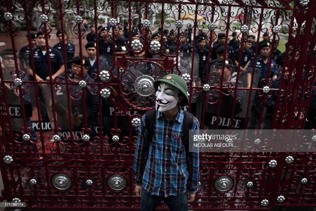A protester wearing a Guy Fawkes mask, stand in front of a gate secured by Thai police officers as he and thousands of protesters gather in Bangkok's shopping district on June 23, 2013. Thousands of people marched through central Bangkok to protest against the former prime minister Thaksin Shinawatra and the current government led by his sister Thai Prime minister Yingluck Shinawatra. AFP PHOTO/ Nicolas ASFOURI