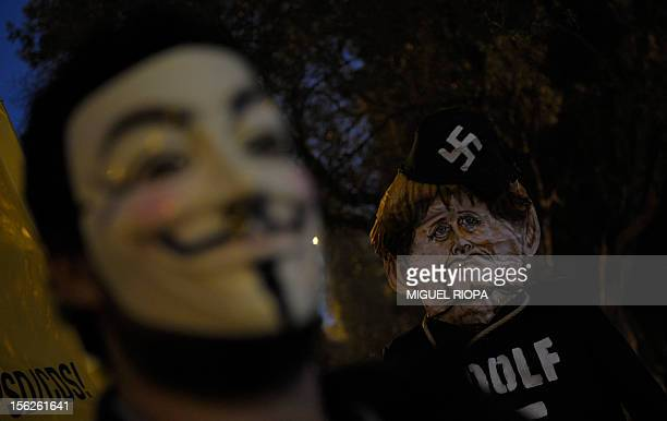 A protester wearing a Guy Fawkes mask stands next to a figure of German Chancellor Angela Merkel wearing a hat with a Nazi swastika symbol during...