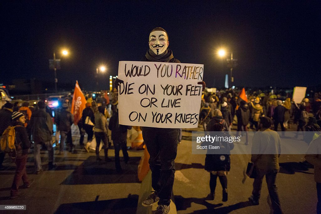 A protester wearing a <a gi-track='captionPersonalityLinkClicked' href=/galleries/search?phrase=Guy+Fawkes&family=editorial&specificpeople=101029 ng-click='$event.stopPropagation()'>Guy Fawkes</a> mask stands on a railing during a protest against the decision by a Staten Island grand jury not to indict a police officer who used a chokehold in the death of Eric Garner in July, on December 4, 2014 in Boston, Massachusetts. The grand jury declined to indict New York City Police Officer Daniel Pantaleo in Garner's death.