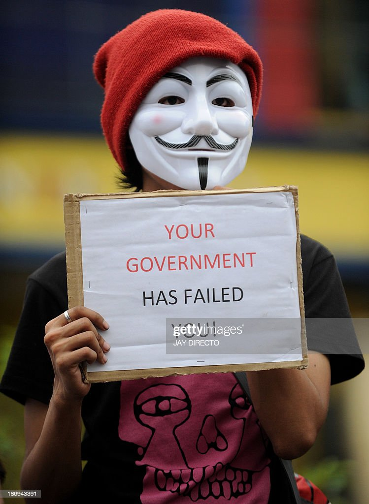A protester wearing a Guy Fawkes masks displays a placard during a rally outside the House of Representatives in suburban Quezon city, north of Manila on November 5, 2013. Some 100 masked members of the hacking group Anonymous Philippines marched on parliament on November 5, denouncing corruption and pledging more cyber attacks, a week after 30 government websites were paralysed. AFP PHOTO / Jay DIRECTO