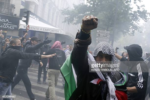 A protester wearing a kaffiyeh and wrapped in a Palestinian flag raises his fist on July 13 2014 in Paris during a demonstration against Israel and...