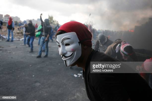 A protester wearing a mask of the anonymous movement takes part in confrontations between Palestinian demonstrators and Israeli security forces at...