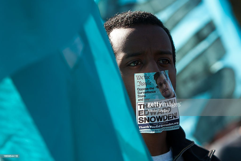 A protester wearing a sticker over his mouth featuring former National Security Agency employee Edward Snowden, listens to speakers during the Stop Watching Us Rally protesting surveillance by the U.S. National Security Agency, on October 26, 2013, in front of the U.S. Capitol building in Washington, D.C. The rally began at Union Station and included a march that ended in front of the U.S. Capitol building and speakers such as author Naomi Wolf and former senior National Security Agency senior executive Thomas Drake.