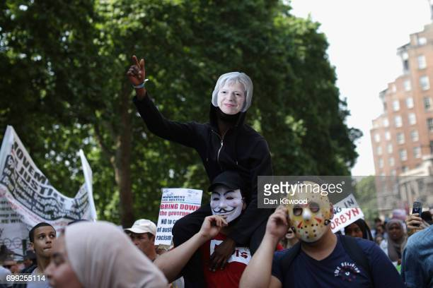 A protester wearing a Theresa May mask rides on the shoulders of a protester wearing a 'V For Vendetta' Guy Fawkes mask as they march towards...