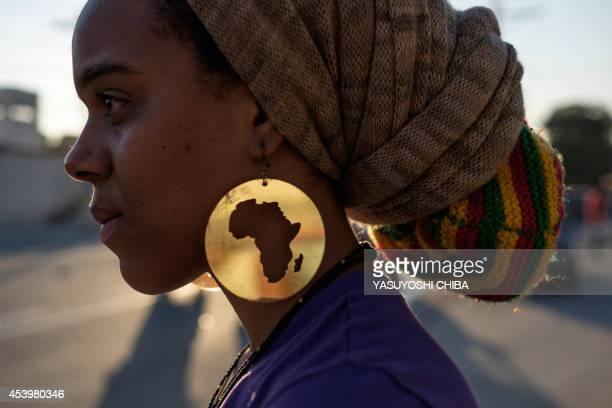 A protester wearing earings with the map of Africa takes part in the International March Against the Genocide of Black People in Rio de Janeiro...
