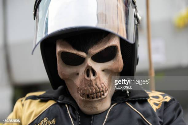 A protester wearing protective gear and a skull mask waits for police to arrive on a blocked road at the main prodemocracy protest site in the...