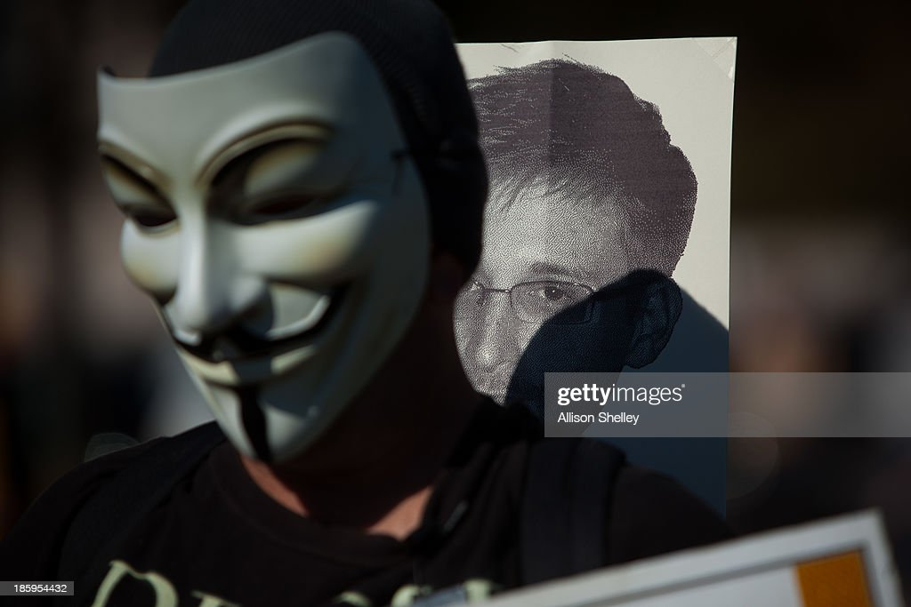 A protester wearing the mask often seen during the Occupy protests marches with a sign featuring the likeness of former National Security Agency...