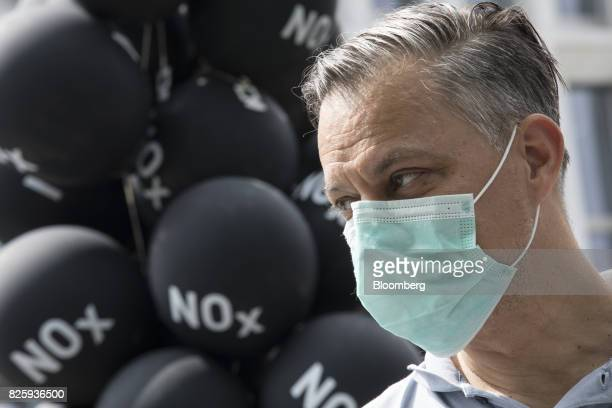 A protester wears a face mask as he stands beside balloons marked with the chemical symbol of nitrogen oxide during an antidiesel fuel protest in...