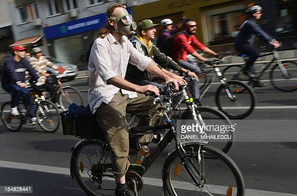 A protester wears a gas mask during a march and protest in Bucharest on October 27 2012 Over 500 cyclist take part in a march demanding the right to...